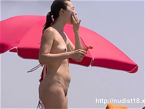 Real beach naturist is stretching on the sand